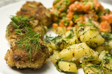 Pork burgers with potatoes, carrot and green peas