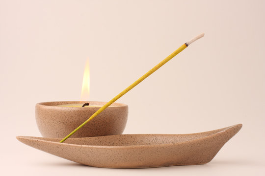 Candle and incense stick in pastel shades