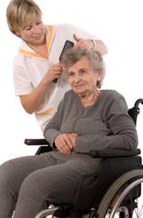 Nurse dressing the hair of a senior woman