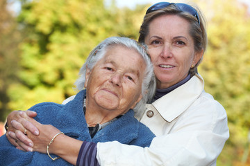 Middleaged woman cuddles her elderly mother