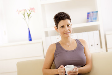 Young woman sitting on sofa at home, drinking coffee.