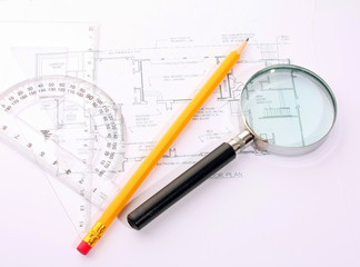 Small magnifier, protractor and pencil on the flat plan