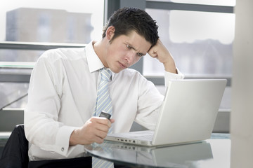 young man confussed at his lap top