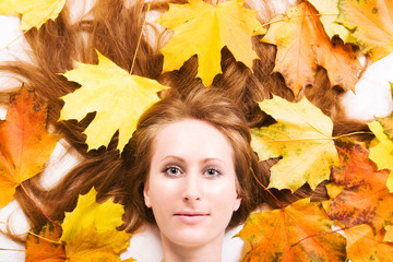 Young woman with autumn maple leaves portrait.