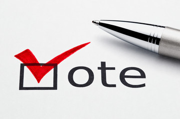 Red checkmark on vote checkbox, pen lying on ballot paper.