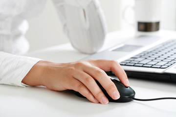 Image of female hand touching computer mouse