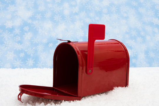 Red mailbox with the flag up sitting on snow