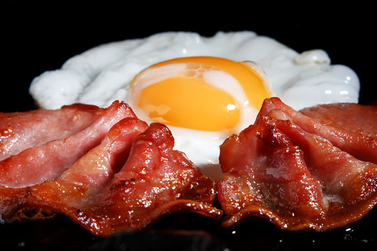 frying egg and two bacon rashers, shallow DOF