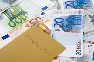 goldenes Sparbuch mit Geldscheinen
