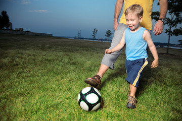 Boy playing football with his dad outdoors at twilight