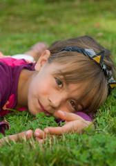 petite fille se reposant dans l'herbe verte