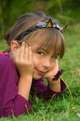 petite fille dans l'herbe déguisée en chat avec sa fleur