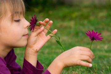 petite fille cueillant des fleurs violettes
