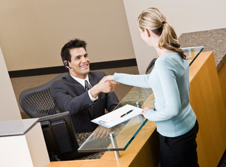 Receptionist greeting woman at front desk and shaking hands