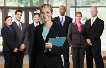 Confident businesswoman posing in front of co-workers
