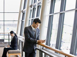 Businesspeople on laptop and text messaging in office lobby