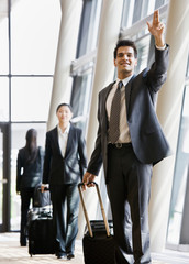 Business traveler pulling suitcase and gesturing to co-worker