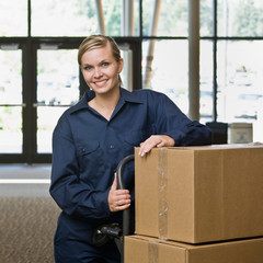 Delivery woman in uniform posing with stack of cardboard boxes