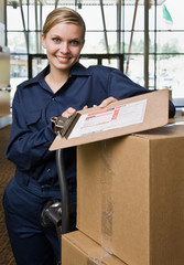 Delivery woman in uniform with stack of cardboard boxes