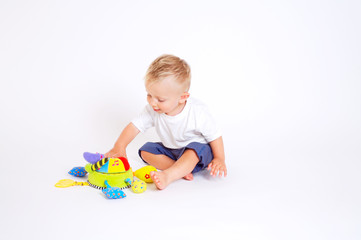 One year old baby boy enjoys playing with toys. Studio Shot.
