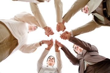 Five business people forming a circle and holding hands,