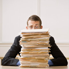 Frustrated businessman looking at pile of file folders