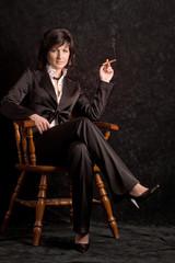 nice young girl is sitting on the chair ang smoking
