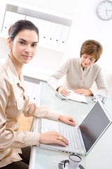 Senior businesswoman and young assistant working