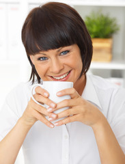 Beautiful business woman holding cup of coffee in her office