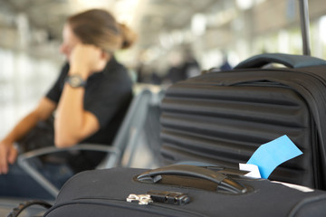 tired woman sleeping behind travel luggage