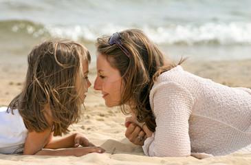 maman et sa fille allongées tendrement sur la plage