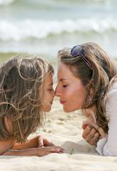 maman embrassant sa fille sur la plage