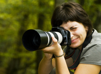 Young female photographer in forest