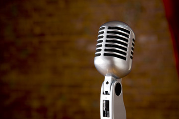 A silver vintage microphone in front of a blurred red brick wall