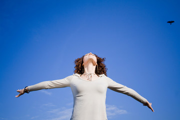 Fototapeta Young woman agains blue sky with arms outstreched obraz