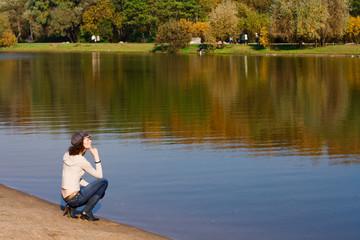 Fototapeta Young pretty woman sitting on the border of a river obraz