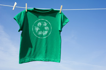 A green t-shirt hanging on a clothesline with the recycle symbol