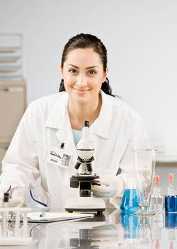 Scientist in lab coat and rubber gloves looking at specimen