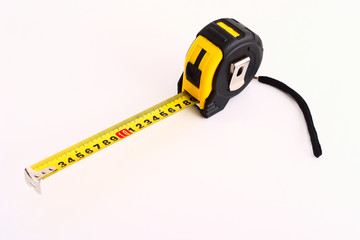 Yellow and black tape measure on white background