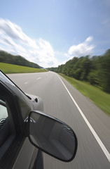 Vehicle, with large rear view mirror, speeds down a country road