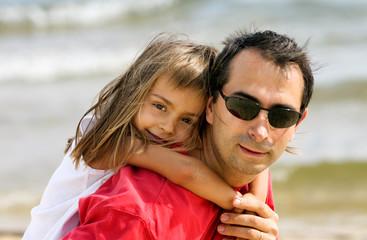 petite fille sur le dos de son papa sur la plage