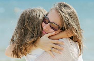 petite fille dans les bras de sa maman sur la plage