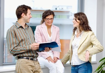 Happy young businesspeople having meeting at office