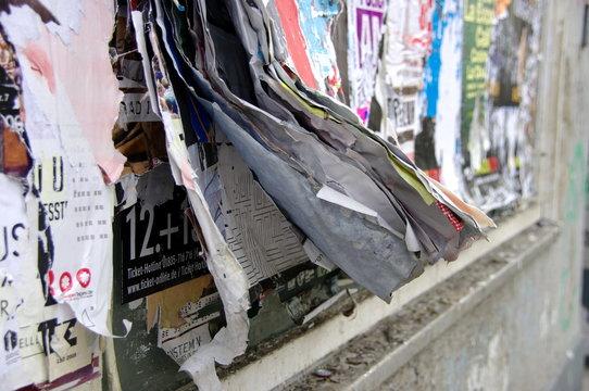 Affiches superposées décollées sur un mur. Rue de Berlin.
