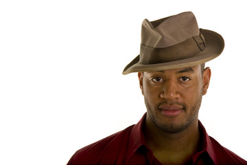 A black man in a red shirt and an old brown hat