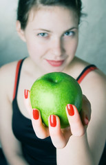 Young beautiful girl holding a green apple