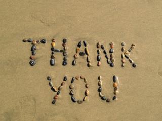 Thank you phrase written on beach sand
