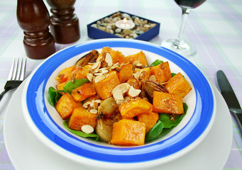 Roasted pumpkin and onion salad with spinach and almonds.