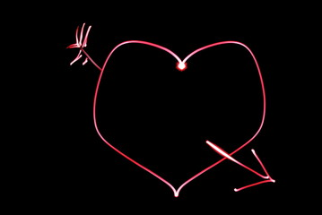 Red heart with arrow on a black background.