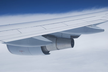 Wing and jet engine of passenger airplane flying.